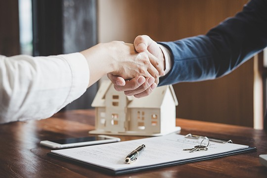 real estate agent and customer shaking hands celebrating finished real estate loan contract